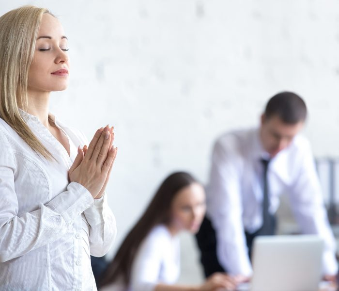 Business and healthy lifestyle concept. Beautiful young office woman meditating and relaxing with closed eyes at workplace. Attractive business lady using stress relief techniques at work. Copy space